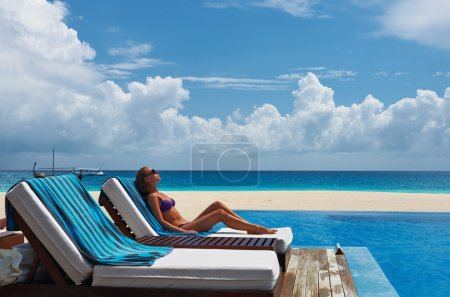 Woman relaxing in chaise lounge at the poolside...