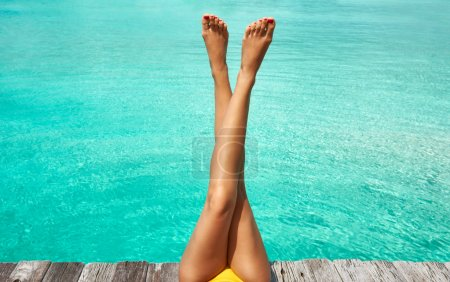Photo for Woman's legs at beach jetty - Royalty Free Image