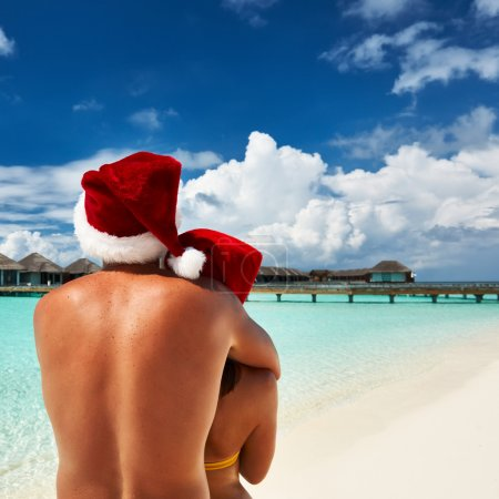 Photo for Couple in santa's hat on a tropical beach at Maldives - Royalty Free Image