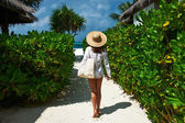 Woman with bag and sun hat going to beach