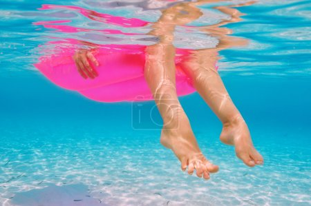 Woman relaxing on inflatable mattress, view from underwater