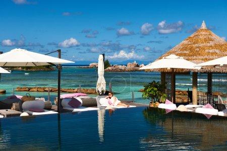 Photo pour Femme relaxante près de la piscine aux Seychelles - image libre de droit