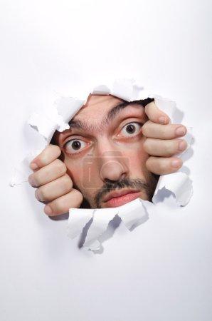 Visage masculin à travers le trou dans le papier