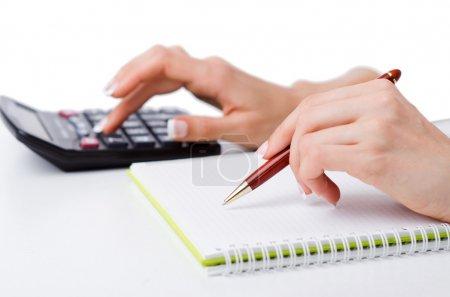 Photo pour Mains travaillant sur la calculatrice - image libre de droit
