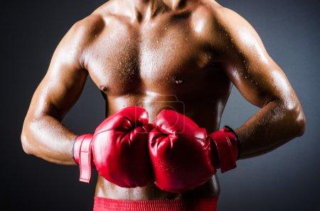 Photo pour Boxer avec gants rouges dans la chambre noire - image libre de droit