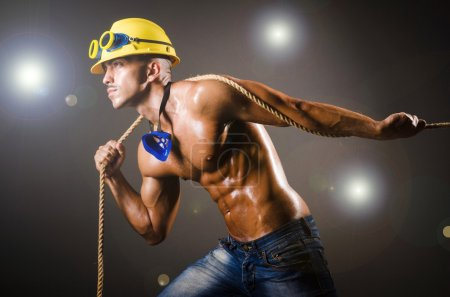 Photo for Nude builder pulling rope in darkness - Royalty Free Image