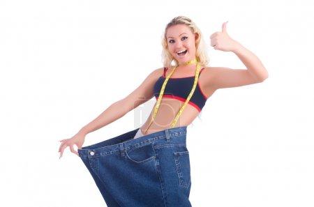 Photo pour Femme en régime concept avec gros jeans avec pouce vers le haut et ruban de mesure - image libre de droit