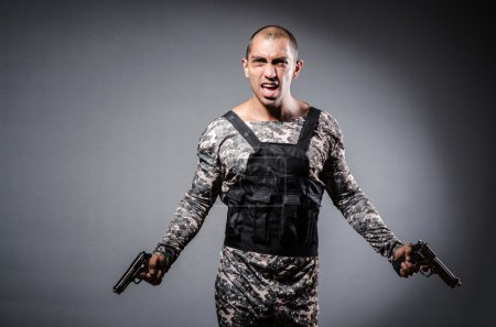Photo for Soldier with guns against dark background - Royalty Free Image