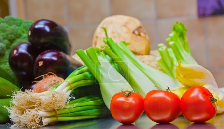 Photo for Fresh tomatoes, eggplants, lattuce and onion on the counter - Royalty Free Image