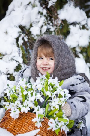Little girl in a winter wood with the big basket of snowdrops