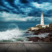 Big ocean wave, lighthouse and wood pier