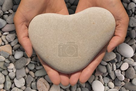 Hands holding a heart-shaped stone