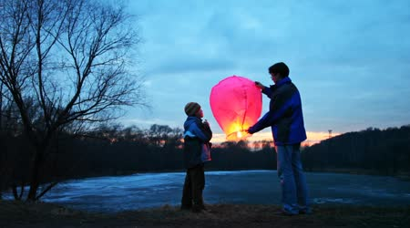 Man holds chinese lantern, son looks at it, then daughter come to them