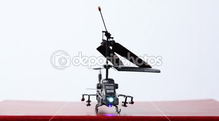 Toy helicopter is on table, its blades start to rotate, then it flies up upwards