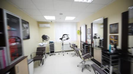 Flying motion of camera in hairdressing salon along armchairs to window