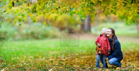 Photo for Mother and her little daughter at beautiful autumn park - Royalty Free Image