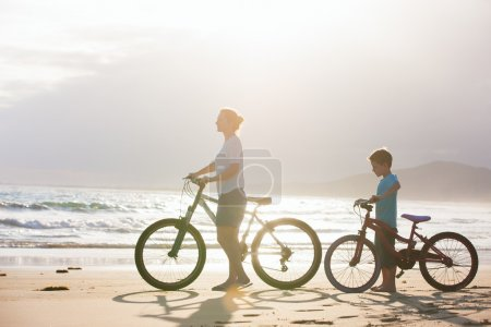 Photo for Mother and son with bikes on a beach at sunset - Royalty Free Image