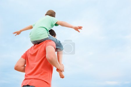 Father carrying his son on shoulders
