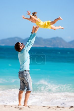 Photo for Happy father and his adorable little daughter at tropical beach having fun - Royalty Free Image