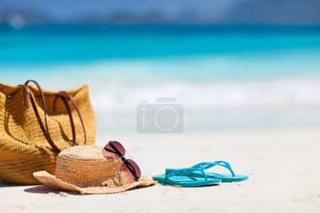 Straw hat, bag, sun glasses and flip flops on a tr...