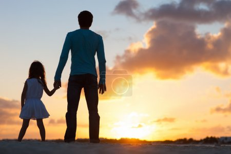Photo for Father and little daughter silhouettes on beach at sunset - Royalty Free Image