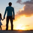 Father and little daughter silhouettes on beach at...
