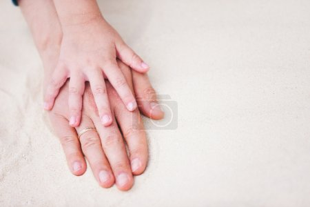 Photo for Close up of father and daughter hands on sand - Royalty Free Image