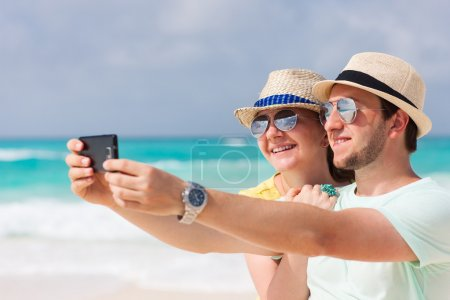 Photo for Yong couple making a self portrait with a mobile phone - Royalty Free Image