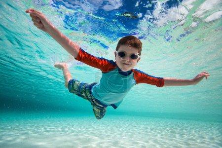 Photo pour Mignon petit garçon nageant sous l'eau dans la mer tropicale - image libre de droit