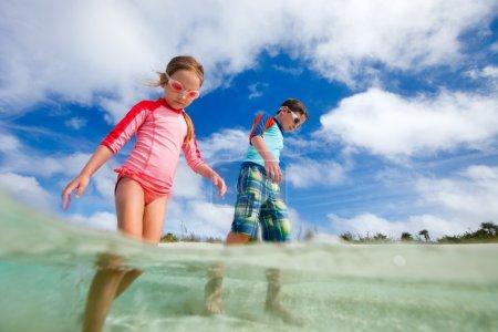 Photo pour Deux enfants jouent à l'eau peu profonde pendant les vacances d'été - image libre de droit