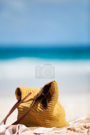 Photo for Close up of a straw bag, sun glasses and towel on a tropical beach - Royalty Free Image