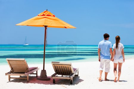 Photo for Back view of a couple on a tropical beach vacation - Royalty Free Image