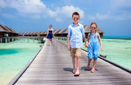 Photo for Cute little kids walking together on wooden jetty at tropical resort - Royalty Free Image