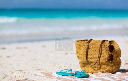 Foto de Vacaciones en la playa cerca. bolso de la paja, gafas de sol, toalla y chanclas en una playa tropical - Imagen libre de derechos