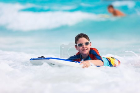 Photo for Little boy on vacation having fun swimming on boogie board - Royalty Free Image