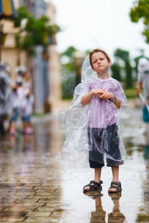 Photo pour Petit garçon en plastique imperméable transparent debout sous la pluie le jour de l'été - image libre de droit