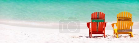 Photo for Two colorful wooden chairs at tropical white sand beach in Caribbean, panorama with copy space perfect for banners - Royalty Free Image