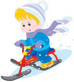Little boy or girl sitting on a snow scooter and sliding down
