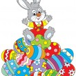 Little rabbit sitting on a pile of colorfully pain...