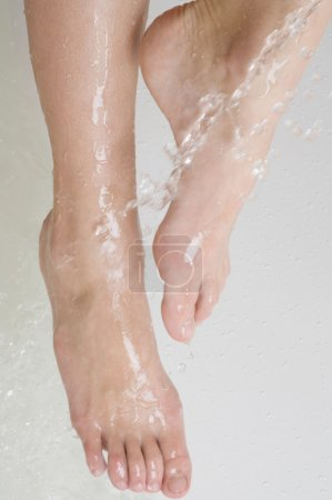 woman's foots and drop's of water