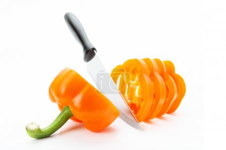 Photo for Sliced orange pepper sharp knife on a white background - Royalty Free Image