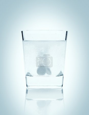 Photo for Glass with two tablets of soluble aspirin on a light blue background - Royalty Free Image