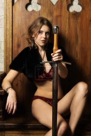 Sexy woman with a sword in a medieval castle