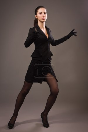 Photo for Spy girl in a black suit shoots a gun - Royalty Free Image