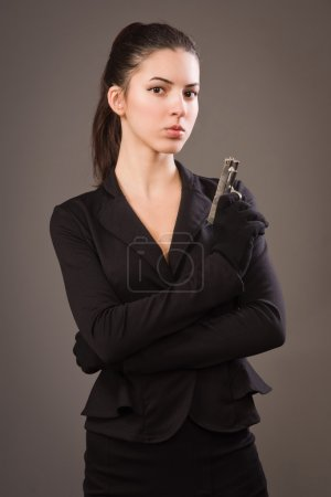 Photo for Spy girl in a black suit with gun - Royalty Free Image