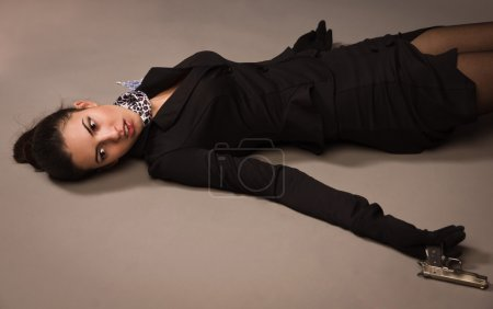 Photo for Detective scene imitation. Woman in a black suit with gun lying on the floor - Royalty Free Image