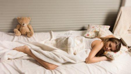 Foto de Chica bonita rubia acostada en la cama - Imagen libre de derechos