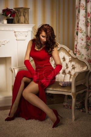 Foto de Hermosa morena con un vestido rojo sentado en el sofá en el interior vintage - Imagen libre de derechos