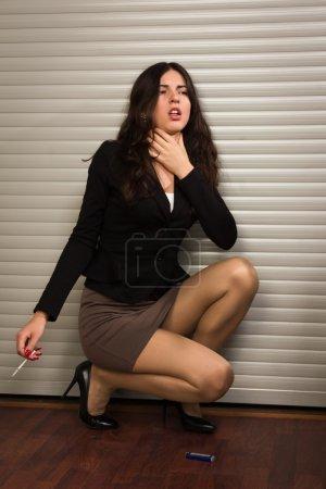 Business woman choking on cigarette smoke