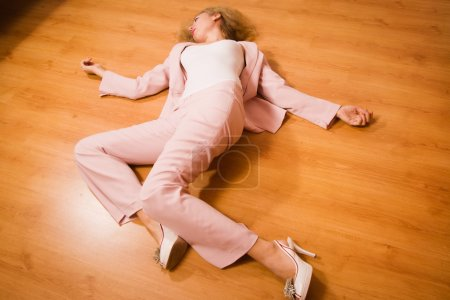 Photo for Crime scene simulation: unconscious business woman lying on the floor - Royalty Free Image